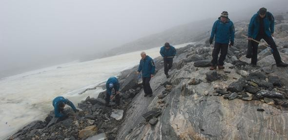 Glacial archaeologists systematically survey the mountainous areas of