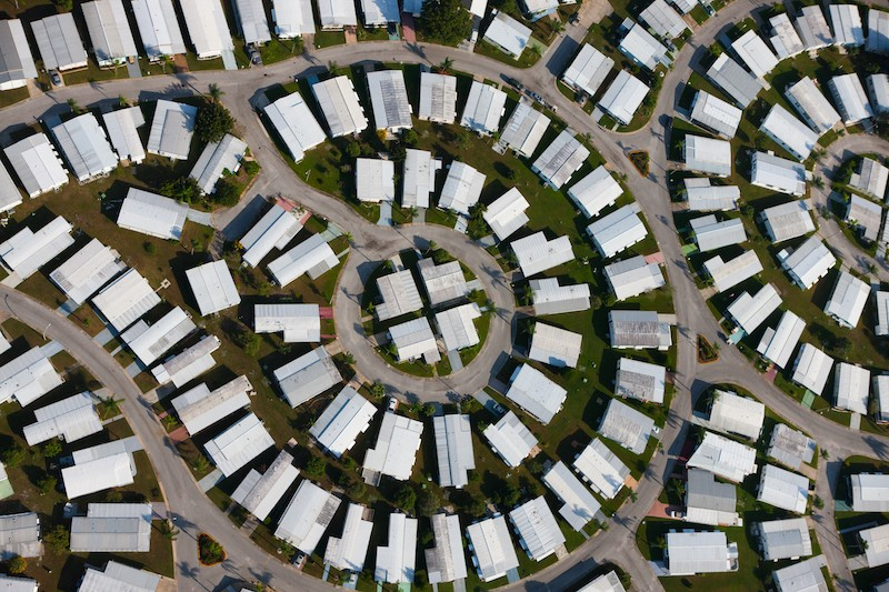 Aerial view of white roofed homes and streets forming circular patterns; St. Pet