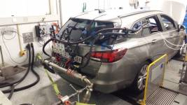 An Opel Astra 1.6 CDTI on Empa's dynamometer test rig: the tubes connect the exh