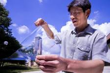 Jay Guo holds a sheet of flexible transparent conductor on the University of Mic