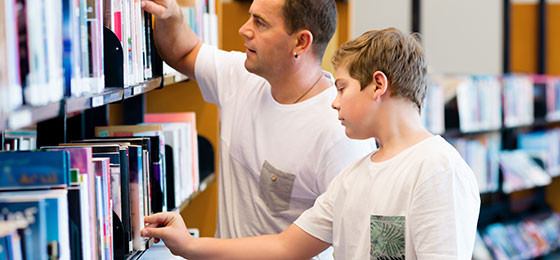 A boy and his father searching for books in the library.