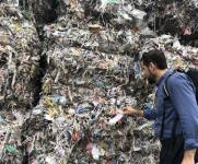 Ali Abbas at a paper recycling plant inspecting piles of plastic waste that have