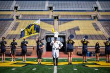 A small number of Michigan Marching Band members pose at the empty Michigan Stad